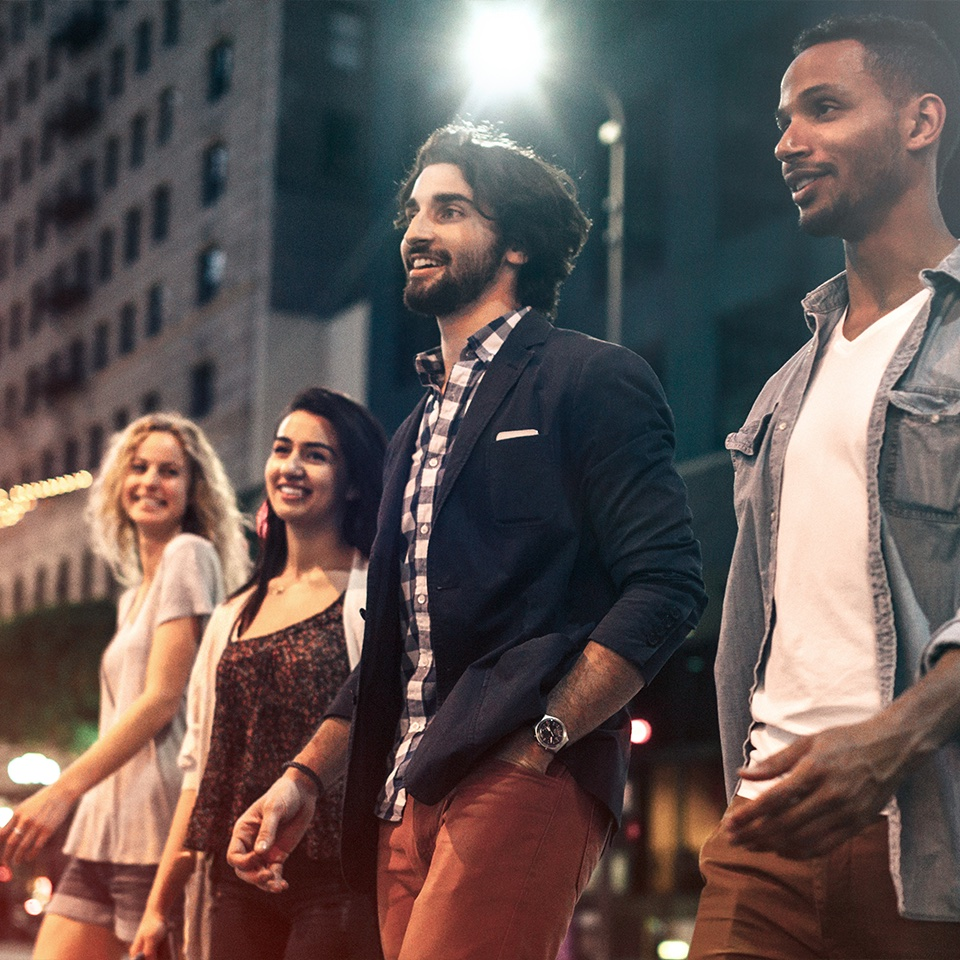 Four friends walking on city street at night