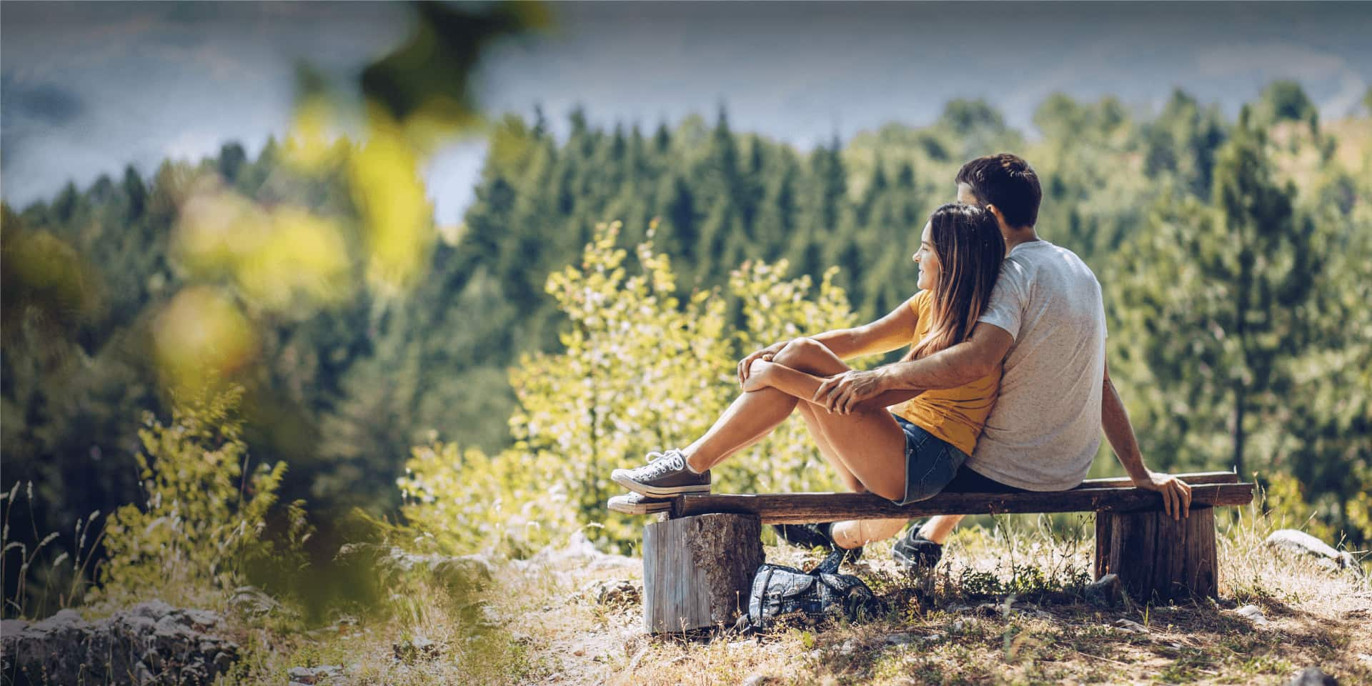 Couple sitting on bench just off hiking trail